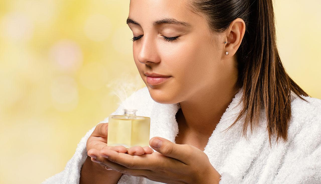 Frau riecht an einer Flasche mit ätherischem Öl