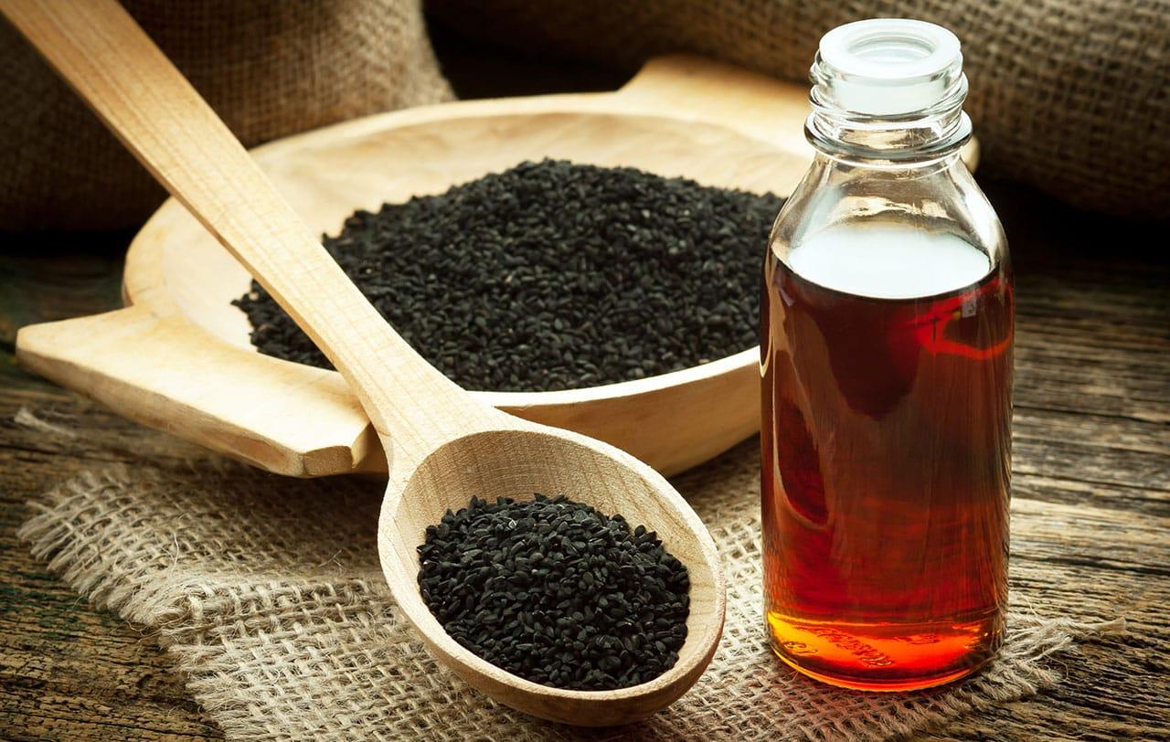 Flasche mit Schwarzkümmelöl neben einer Holzschale und einem Holzlöffel auf einem Tisch