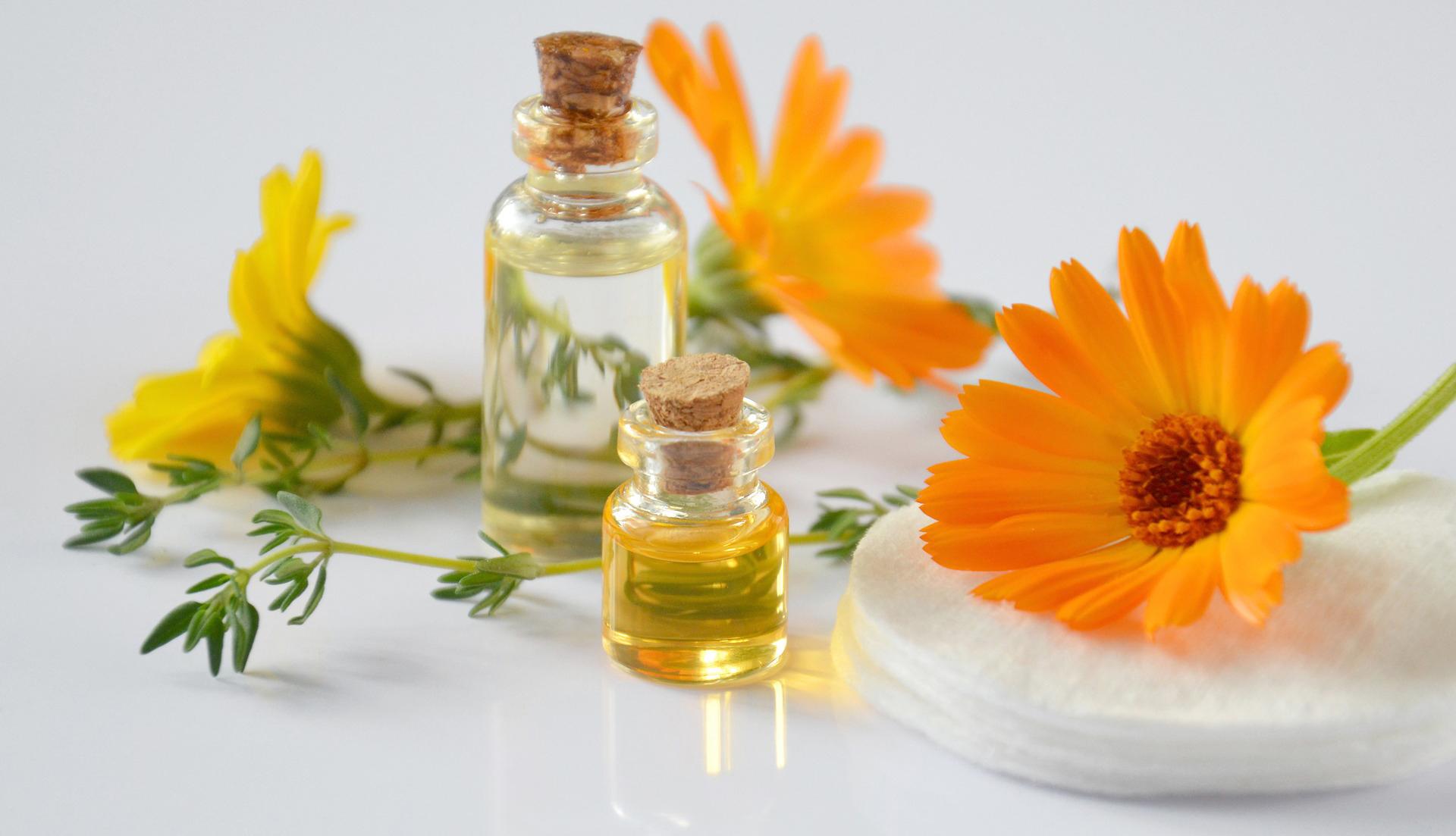 Ätherische Öle mit Blumen im Hintergrund