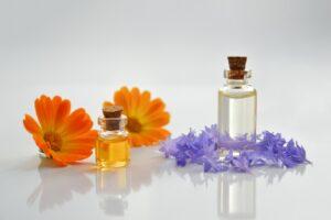 kleine Fläschchen mit ätherischen Ölen und Blumen