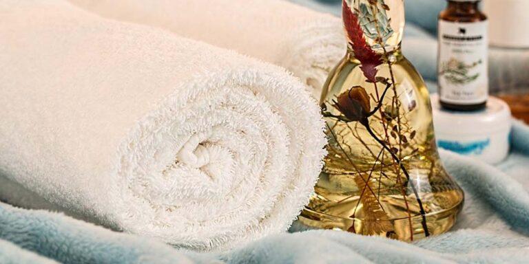 Ein Fläschchen mit ätherischem Öl neben einem Handtuch