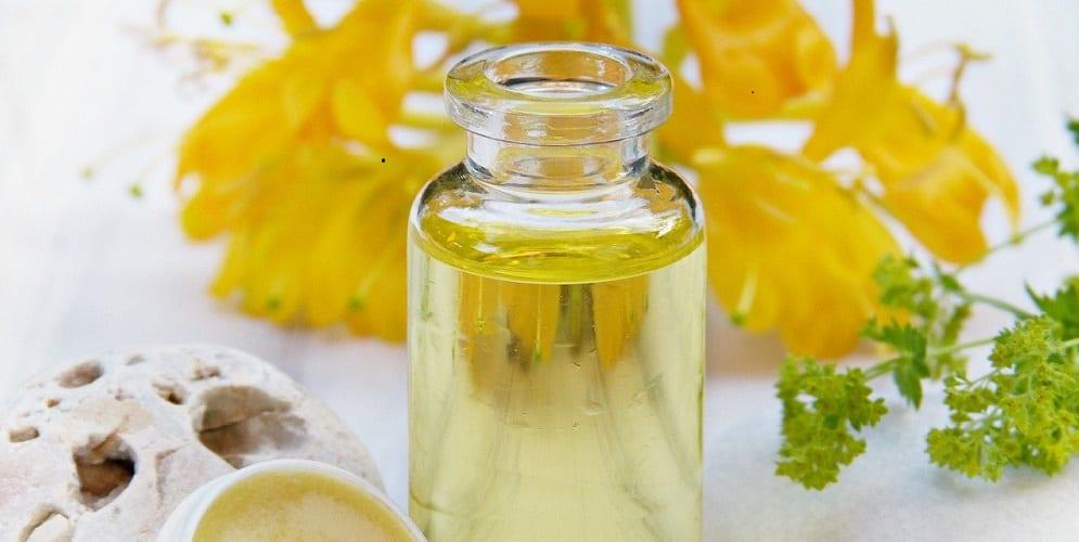 Fläschchen mit ätherischem Öl vor gelben Blüten