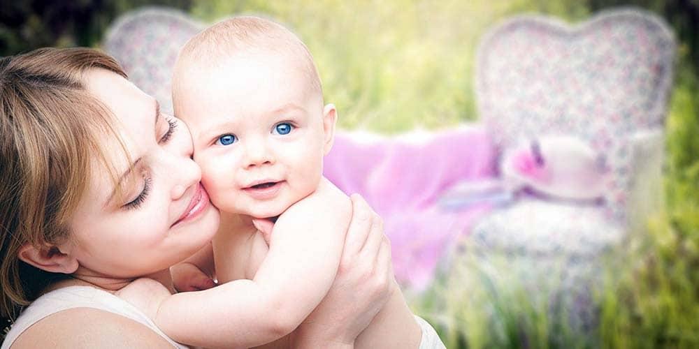 Mutter hält ihr Baby auf einer Wiese im Arm