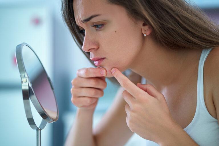 Frau vor Spiegel drückt einen Pickel aus
