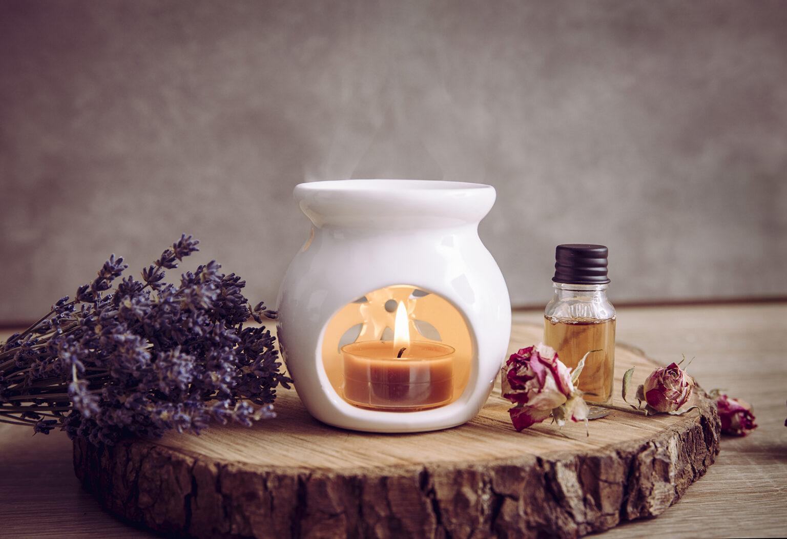 Duftlampe auf einem Stück Holz mit Lavendel und einer Flasche ätherischem Öl