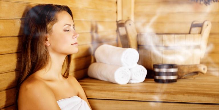 Junge Frau sitzt in einer Sauna