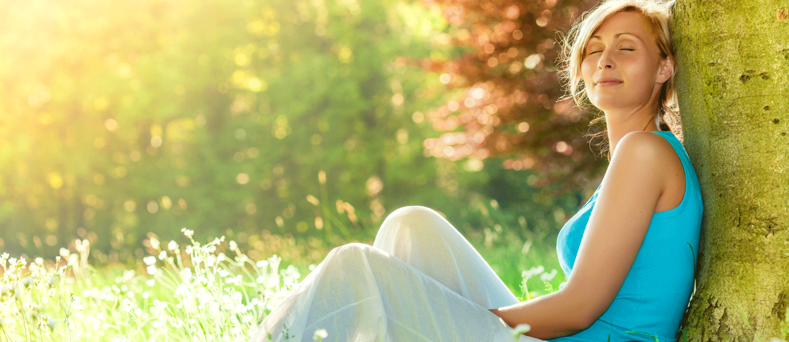 Junge Frau lehnt auf einer Wiese an einem Baum