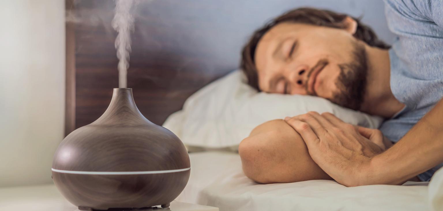 Junger Mann schläft in einem Bett, neben ihm sprüht ein Diffuser