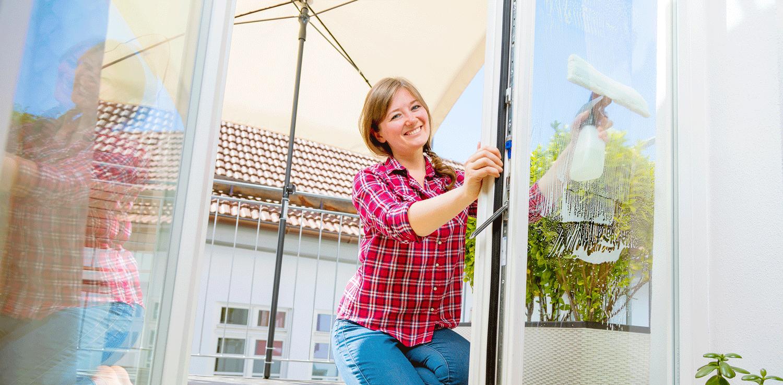 Junge Frau reinigt das Fenster eines Balkons