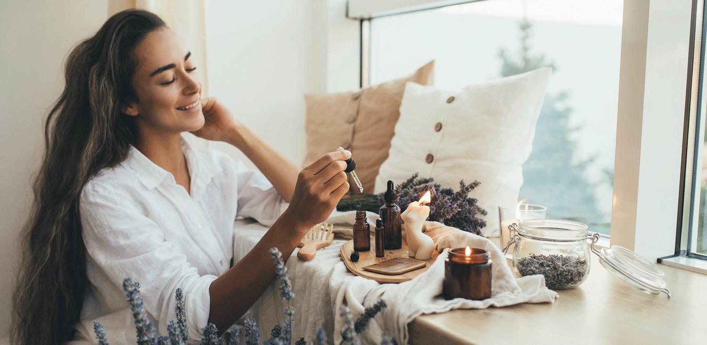 Junge Frau sitzt am Fenster vor ihr ein paar Ätherische Öle und Lavendel